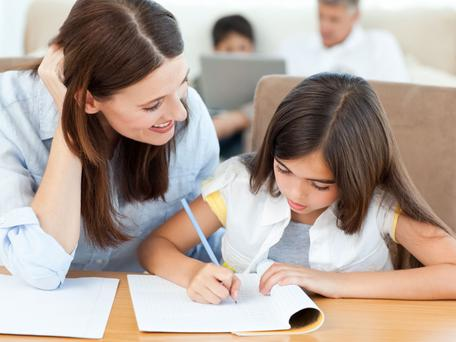 A mum helping her daughter out with homework but thousands of parents don't check their child's schoolwork