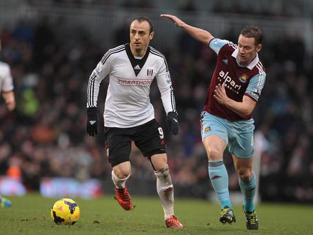 Fulham's Dimitar Berbatov is tackled by West Ham United's Kevin Nolan during the Barclays Premier League match at Craven Cottage, London on Wednesday