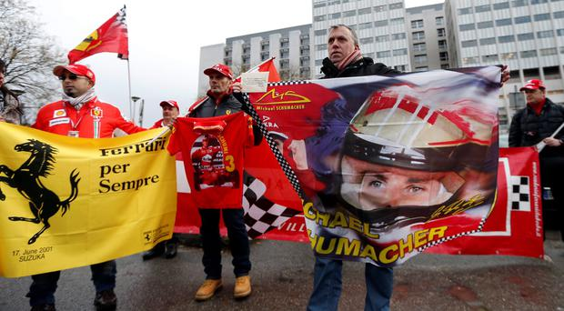 Ferrari fans from France, Italy and Germany attend a silent 45th birthday tribute to seven-times former Formula One world champion Michael Schumacher in front of the CHU hospital emergency unit in Grenoble this morning