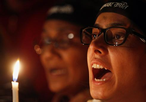 A demonstrator shouts slogans while holding a candle during a candlelight vigil to mark the first death anniversary of the Delhi gang rape victim, in New Delhi December 29, 2013. A 23-year-old woman was gang-raped on a moving bus in Delhi December 16, 2012, beaten and then pushed out onto the street along with her male companion. She died December 29, 2012 amid an outpouring of anger across India. Four men were sentenced to death while a teenager was sentenced to juvenile custody. REUTERS/Anindito Mukherjee