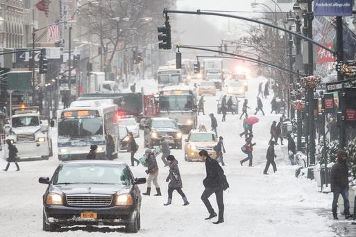 Pedestrians brave wind and snow as they cross Fifth Avenue, Friday, Jan. 3, 2014, in New York. New York City public schools were closed Friday after up to 7 inches of snow fell by morning in the first snowstorm of the winter.
