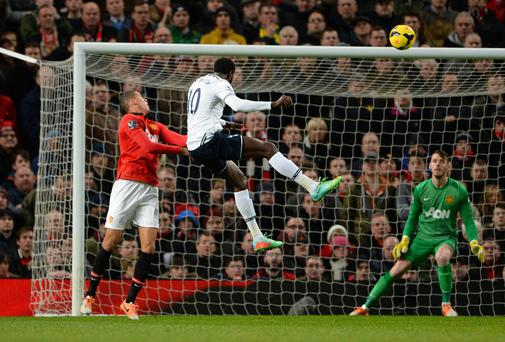 Emmanuel Adebayor rises above Chris Smalling to open the scoring for Spurs at Old Trafford REUTERS