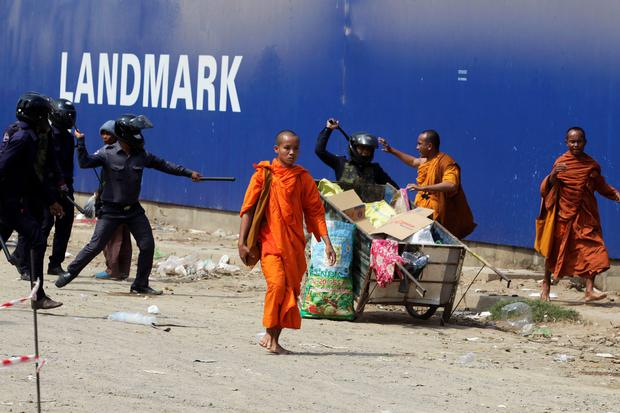 Security guards chase away Buddhist monks from a camp occupied by anti-government demonstrators in Phnom Penh
