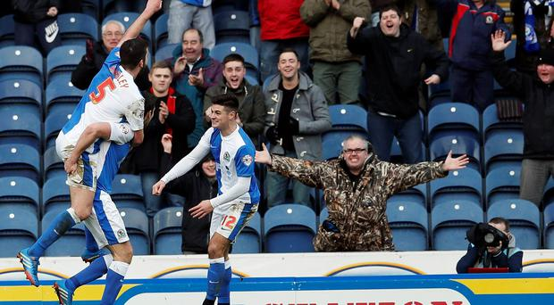 Blackburn Rovers' Grant Hanley (L) jumps on a teammate's back as they celebrate Scott Dann's goal during their FA Cup third round match against Manchester City at Ewood Park in Blackburn.