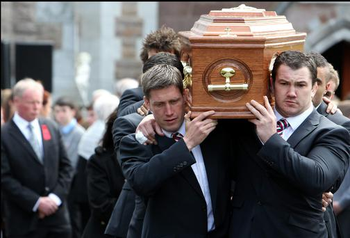 Ronan O'Gara helps carry the body of Donal Walsh from St Johns Church in Tralee Co Kerry yesterday. Pic Steve Humphreys