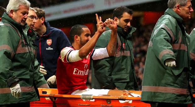 The injured Theo Walcott of Arsenal makes a 2-0 gesture to the Tottenham fans as he is stretchered off the pitch during the Budweiser FA Cup third round match between Arsenal and Tottenham Hotspur