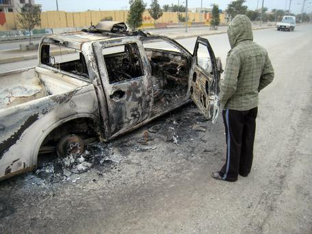 A man looks at a burned police vehicle in the main street of Fallujah after clashes between Iraqi security forces and al-Qaeda fighters in Fallujah