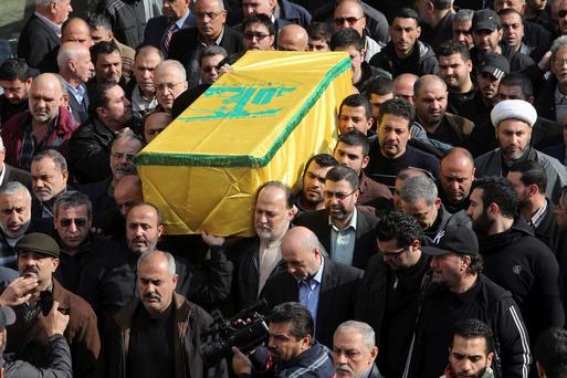 Lebanon's Hezbollah members and relatives carry the coffin of Adnan Awale, a man who was killed by a car bomb explosion which occurred on Thursday