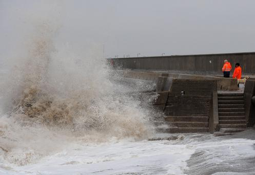 People watch the waves at Cleveleys, Lancashire as stormy weather continues across parts of the country