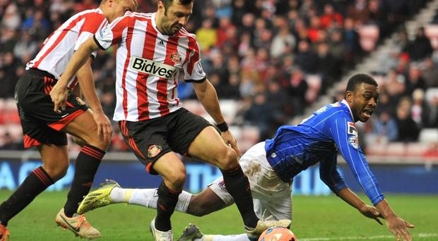 Carlisle's David Amoo(right) tryies to claim a penalty after a tackle in the box by Sunderland's Andrea Dossena during the FA Cup Third Round match at The Stadium of Light.