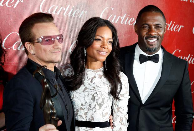 Bono poses with actors Naomi Harris and Idris Elba (R), while he holds the Sonny Bono Visionary Award the band received at the 2014 Palm Springs International Film Festival Awards Gala in Palm Springs. Photo: Reuters