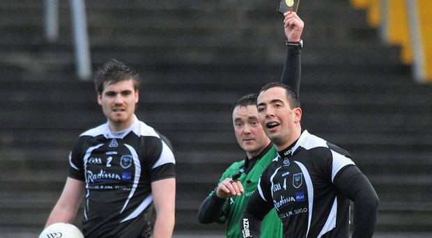 Referee Paddy Neilan issues the black card to Sligo's Neil Ewing during their FBD League clash in Tuam Stadium Ray Ryan / SPORTSFILE