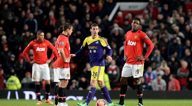 Manchester United's Javier Hernandez (left) and Danny Welbeck (right) stand dejected after Swansea City score a late winner
