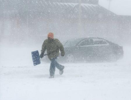 A man carrying a snow shovel walks along Market Street in Champaign, Illinois, on Sunday, Jan. 5, 2014. AP Photo/The News-Gazette, Holly Hart