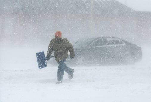A man carrying a snow shovel walks along Market Street in Champaign. Photo: AP Photo/The News-Gazette, Holly Hart