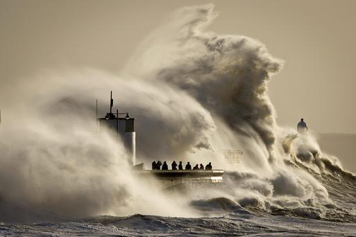 People watch and photograph enormous waves as they break on Porthcawl harbour, South Wales, where very strong winds and high seas create dangerous weather conditions. Photo: Ben Birchall/PA Wire