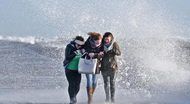 Katie Nash, Tracy Prunty and Pippa Hartridge brave the swell and waves on the Great South Wall, Dublin. Picture: Colin Keegan