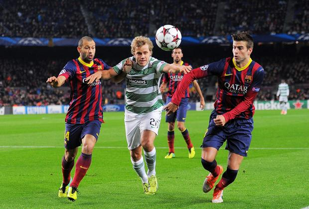 Teemu Pukki of Celtic FC gets between Gerard Pique and Javier Mascherano of FC Barcelona
