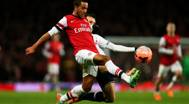 Theo Walcott of Arsenal is tackled by Vlad Chiriches of Spurs during the FA Cup third round match between Arsenal and Tottenham Hotspur