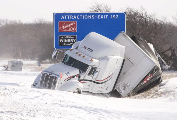 A wrecked semi truck sits in the ditch on the eastbound side of I-74 west of St. Joseph, Illinois