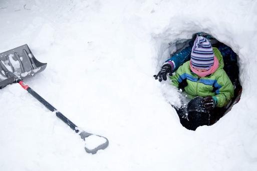 Megan Spencer, 14, and Brooke Spencer, 9, front, test out a snow fort on Monday, Jan. 6, 2014, at their home in Grand Blanc, Mich. (AP Photo/The Grand Rapids Press, Michelle Tessier)