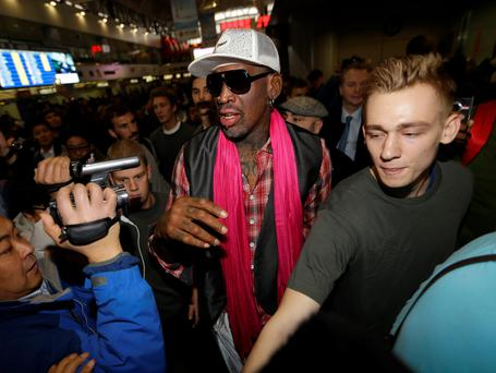Former NBA basketball player Dennis Rodman (C) is surrounded by journalists