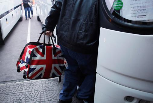 A man carrying a bag adorned with the colours of Britain's Union Jack flag steps into a bus departing from Sofia's central bus station to London