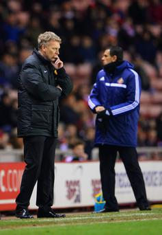 David Moyes manager of Manchester United and Sunderland manager Gustavo Poyet look on during the Capital One Cup Semi-Final first leg