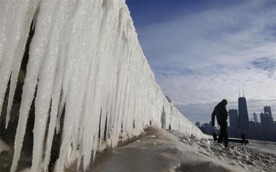 A man walks beside a frozen wall on a beach in Chicago, Illinois, January 7, 2014. REUTERS/Jim Young