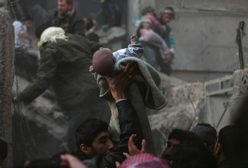 Men hold up a baby who survived what activists say was an airstrike by forces loyal to Syrian President Bashar al-Assad, in the Duma neighbourhood of Damascus yesterday.