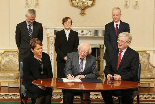 New High Court judge Bronagh O'Hanlon watches President Michael D, Higgins sign her appointment at Aras an Uachtarain today, as Tanaiste Eamon Gilmore sits beside him. At the back, from left, are Adrian O'Neill, Secretary-General to the President; the Attorney General Marie Whelan and Philip Hamell, Assistant Secretary, Department of the Taoiseach. Photo: Tom Burke
