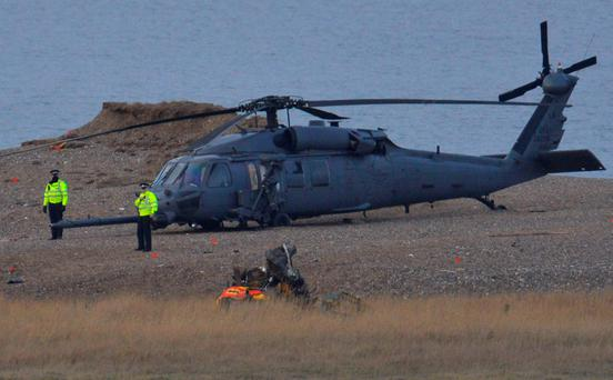 Police officers stand by a Pave Hawk helicopter, at the scene of a helicopter crash on the coast near the village of Cley next the Sea in Norfolk, eastern England