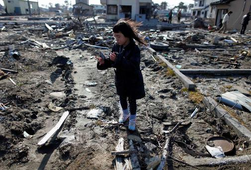 A girl visits the spot where her house was washed away by the tsunami.