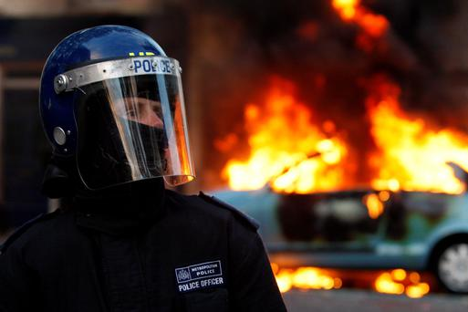 A riot police officer stands in front of a burning car during riots in Clarence Road, Hackney
