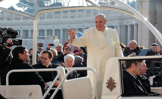 Fabian Baez, a priest from a church in downtown Buenos Aires, sits in the popemobile as Pope Francis arrives to lead the Wednesday general audience in Saint Peter's square at the Vatican