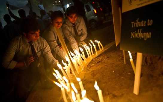 Indian students take part in a candle-light vigil to mark the anniversary of the Delhi gang rape victim