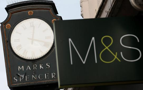 Marks & Spencer signs are seen outside outside a store in London January 8, 2014. The head of British retailer Marks and Spencer, Marc Bolland, said the company's step-by-step approach to improve general merchandise sales was working despite figures showing the 10th consecutive quarter drop in clothing sales. Photograph taken on January 8, 2014. REUTERS/Stefan Wermuth (BRITAIN - Tags: BUSINESS)