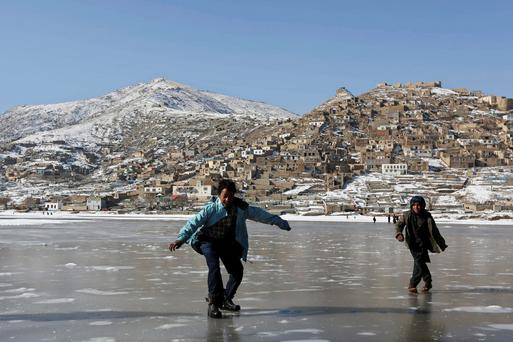 Afghan children play on a frozen lake in Kabul