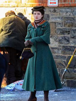 Pictured in a heavy, full-length coat with orange trimmings and a woollen scarf, Eve Hewson attempted to warm her hands from the freezing temperatures.