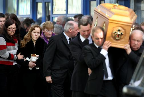 Rebecca holds a toy at the funeral of Martin and Clarissa.