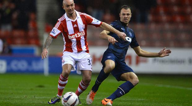 Stephen Ireland (L) of Stoke City competes with Jonny Evans of Manchester United