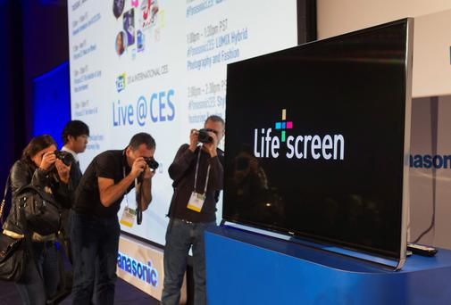 Journalists take photos of a Panasonic television with Panasonic