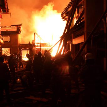 Firefighters fortify a wooden building while a fire ravages ancient Dukezong town in Shangri-la county