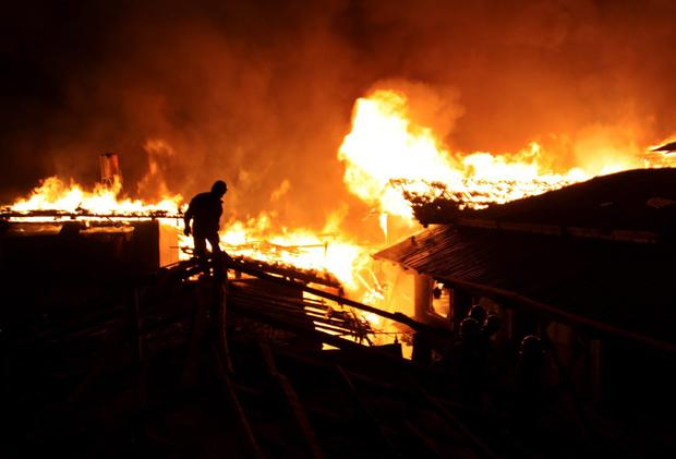 A firefighter works on a roof of a wooden building while a fire ravages ancient Dukezong town in Shangri-la county, in southwestern China's Yunnan province.