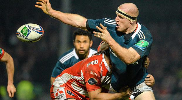Munster talisman Paul O'Connell offloads as he is tackled by Gloucester's Sila Puafisi