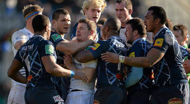 Brian O'Driscoll, Leinster, is restrained by Castres' Max Evans, left