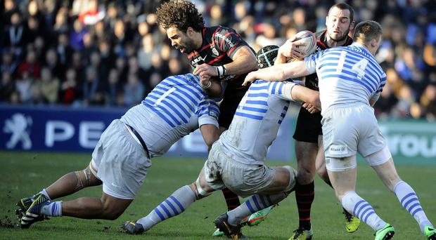 Toulouse's French scrum-half Jean-Marc Doussain (R) is tackled by several Saracens' players