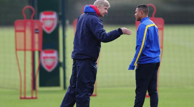 Arsenal manager Arsene Wenger talks with player Serge Gnabry during a training session