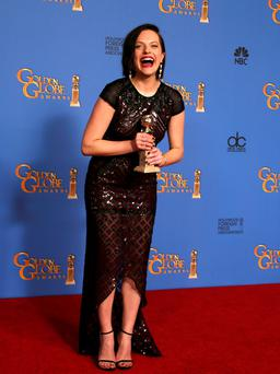 """Actress Elizabeth Moss poses with her award for Best Actress in a Mini-Series or TV Movie for her role in """"Top of the Lake"""" backstage at the 71st annual Golden Globe Awards in Beverly Hills, California January 12, 2014. REUTERS/Lucy Nicholson (UNITED STATES - Tags: ENTERTAINMENT) (GOLDENGLOBES-BACKSTAGE)"""