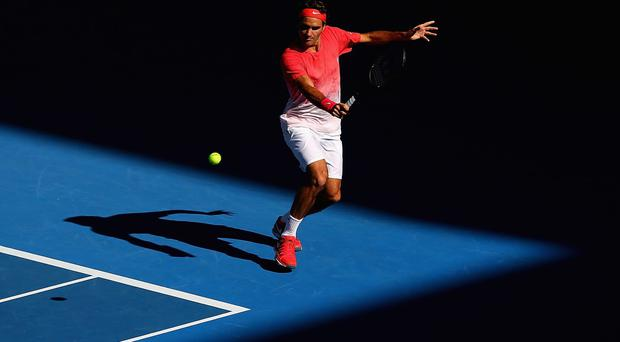 Roger Federer of Switzerland plays a backhand during practice